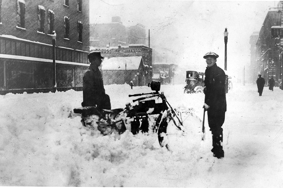 Motorcycle stuck in snow on 9th Street near Idaho Street in 1919. Man on the right is Roy Thompson. McCarty Building on the left. Photo courtesy ISHS 73-205-5