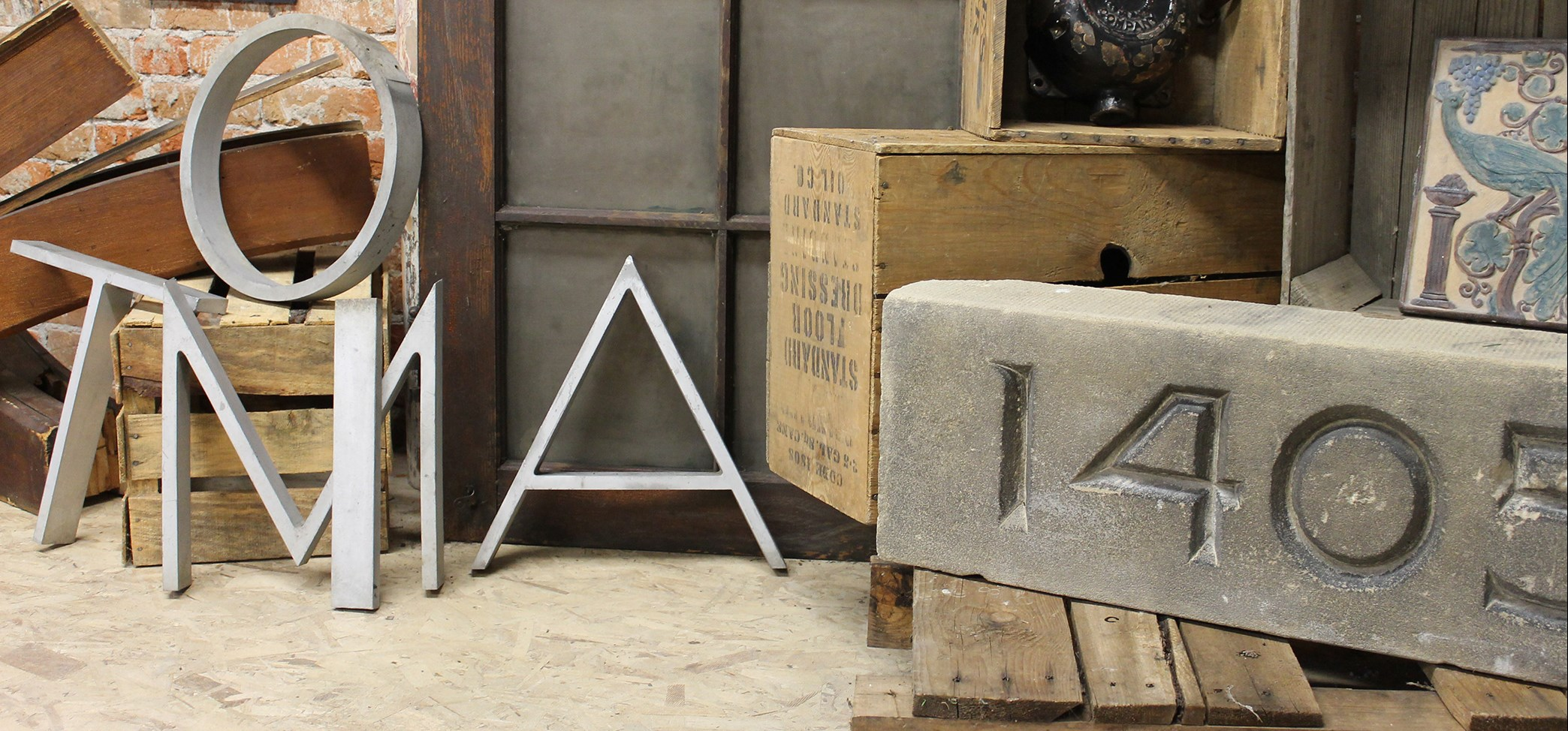 Header image of crates, bricks, and large metal letters